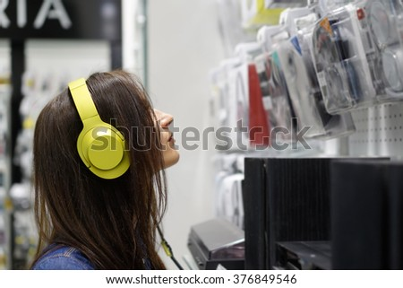 Beautiful girl with yellow headphones in some shop - stock photo