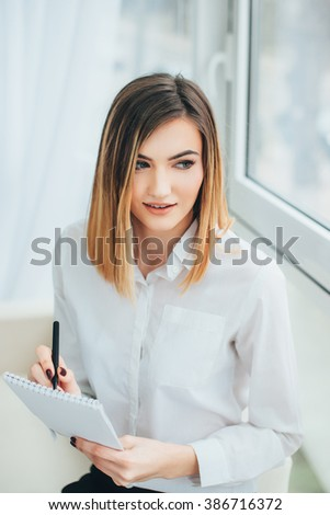 Beautiful girl working in the office. Blonde works and writes in a notebook. Business Projects. Student before an exam. Girl is studying
