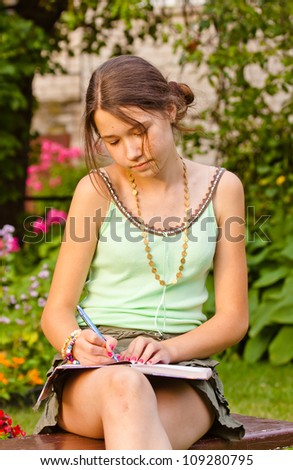 Beautiful girl writing into her diary