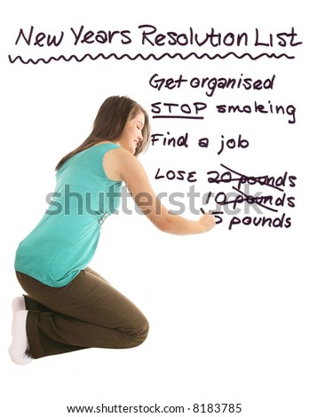beautiful girl writing out a New Years resolutions list on white background - stock photo