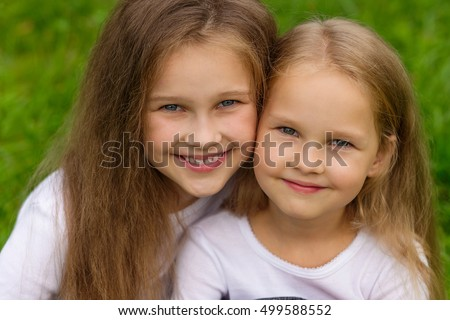 Beautiful girlfriend resting on the nature. Two cute sisters posing in the park