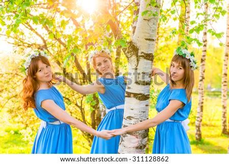 beautiful girlfriend standing around the trunk of a birch - stock photo