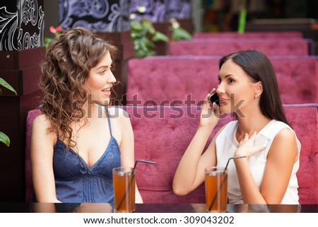 Beautiful girls are sitting at the table in cafe. They are drinking juice and smiling. One girl is talking on the phone with aspirations. Her friend is looking at her with curiosity