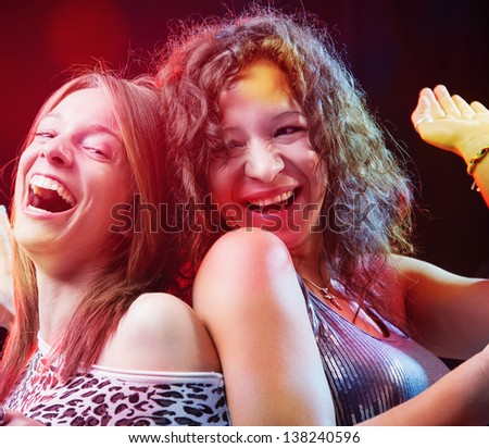 Beautiful girls dancing and having fun in the nightclub - stock photo
