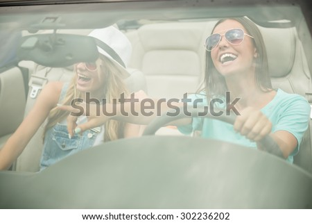 Beautiful girls in sunglasses driving on cabriolet, looking away and having fun. - stock photo