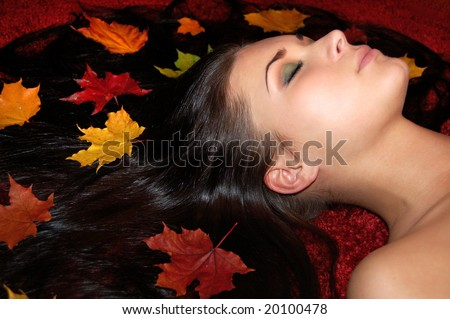 Beautiful girls long dark hair decorated with autumn leaves