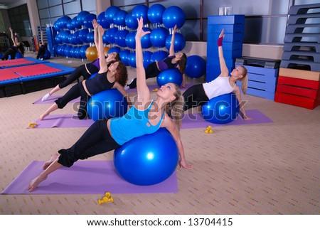 Beautiful girls meditating in fitness club - stock photo