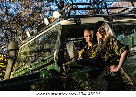 Beautiful girls on camouflage outfit, teamwork and off-road vehicle - stock photo