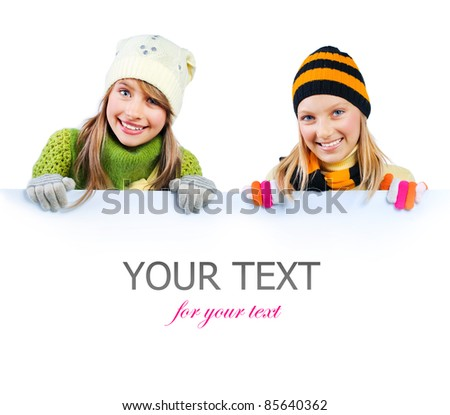 Beautiful Girls peeking from behind blank sign billboard. Space for Your Text - stock photo