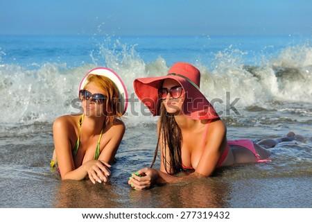 Beautiful girls resting at the sea - stock photo