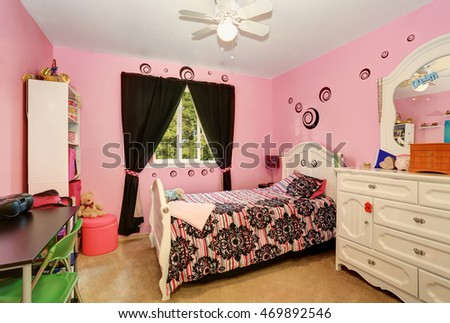 Beautiful girls room in bright pink color with carved wood bed and toys. Northwest, USA
