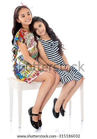 Beautiful girls sisters dressed in short summer dresses sitting on the couch-Isolated on white background - stock photo