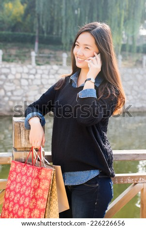 Beautiful girls taking phone calls. Shopping and leisure - stock photo