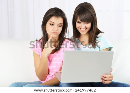 Beautiful girls twins sitting on sofa with notebook