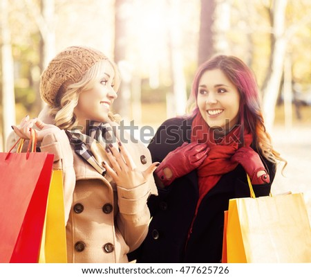 Beautiful girls walking in park with colorful bags. Sunny autumn day.