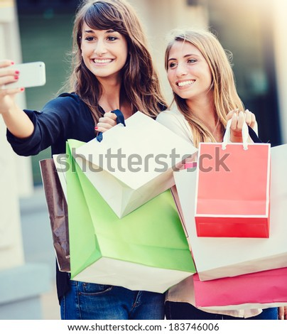 """Beautiful girls with shopping bags taking a """"selfie"""" with their cell phone - stock photo"""