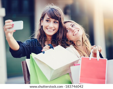 "Beautiful girls with shopping bags taking a ""selfie"" with their cell phone - stock photo"