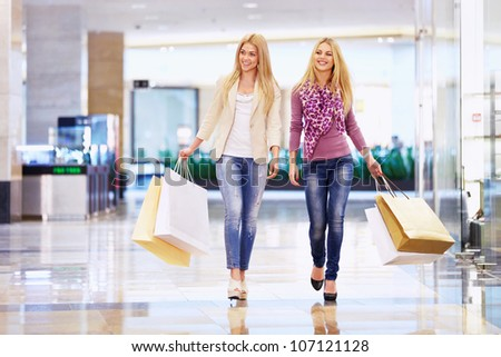 Beautiful girls with shopping bags walking in the store