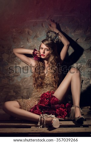 Beautiful glamorous brunette girl with curly long hair. Studio shot. Bright makeup with red lipstick in high-heels. Beauty. Sexy girl in gold underwear, dress. With red roses. Queen in crown. - stock photo