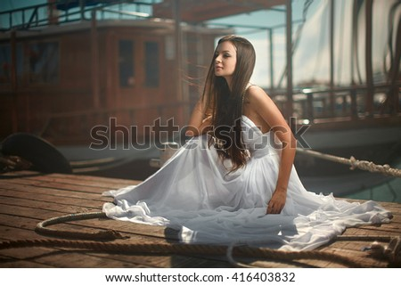 Beautiful, glamorous woman, girl sitting at pier in yacht club near sail boats. Fashion, magazine picture.