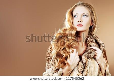 Beautiful glamorous woman in fur coat posing at studio. - stock photo