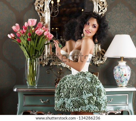 Beautiful Glamorous Woman in Retro Interior with Vase of Flowers. Reflection - stock photo