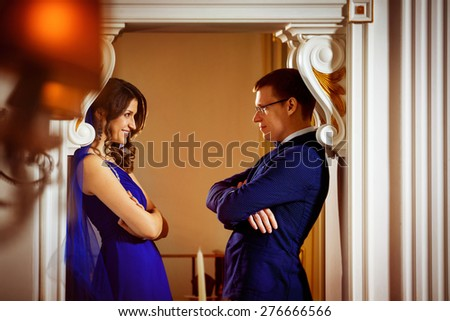 Beautiful glamour couple is standing and looking at each other in arch of a luxury restaurant. Concept of love and rich life. - stock photo