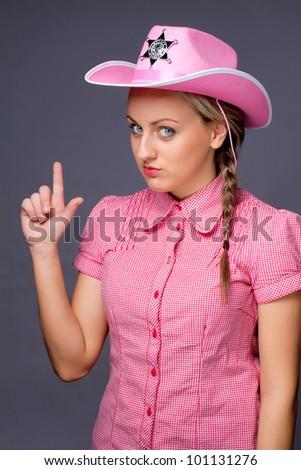 Beautiful glamour cowboy showing gun by fingers - stock photo