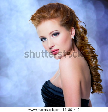 Beautiful glamour red-haired woman with bright make-up looking at camera, isolated on white. Profile portrait