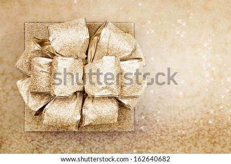 Beautiful gold Christmas gift against a magical golden background with copy space. - stock photo