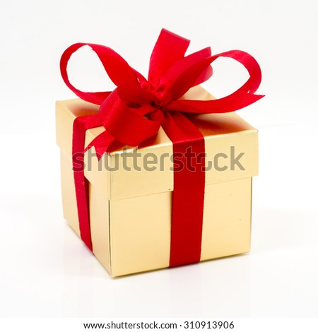 Beautiful gold present box with red bow and ribbons on white backgound - stock photo