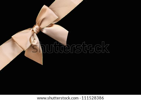 Beautiful gold ribbon gift bow with golden trim isolated on black background - stock photo