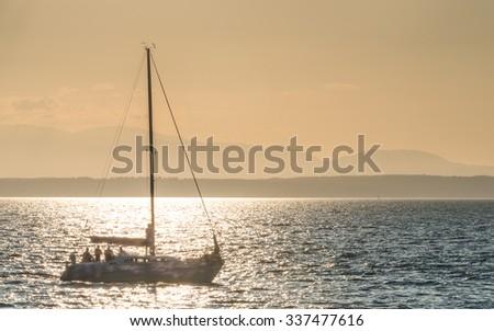Beautiful gold sunset with a sailboat sailing  - stock photo