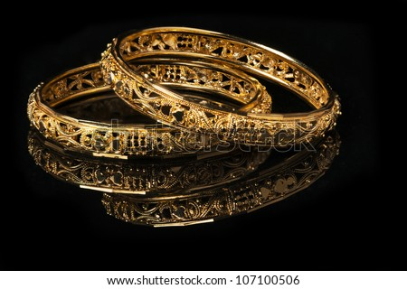 Beautiful golden bangles isolated on black background - stock photo