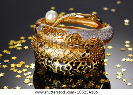 Beautiful golden bracelets on grey background - stock photo