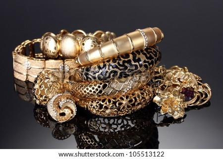 Beautiful golden bracelets, rings and jewelry on grey background - stock photo