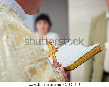 Beautiful golden cross in male hands of priest wearing gold robe on ceremony in christian cathedral church, holy sacramental event. Priest Holding A Bible - stock photo
