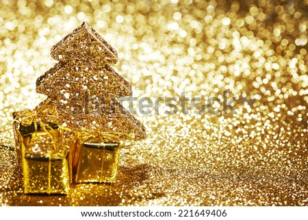 Beautiful golden decorative christmas tree and gifts on golden glitter background