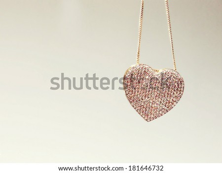 Beautiful golden necklace in a shape of heart with precious gems - diamonds - stock photo