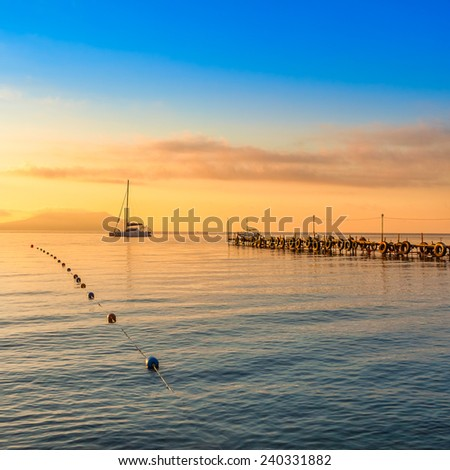 Beautiful golden sunset above the sea and mountain - stock photo