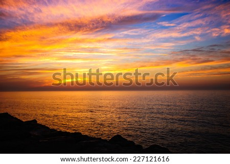 Beautiful golden sunset in the sea with saturated sky and clouds. Reflection in the water. Rocky coastal line. Peaceful serene landscape. Nature background. - stock photo