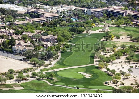 Beautiful golf course next to a luxury resort as viewed from a helicopter - stock photo