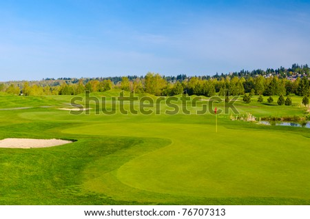 Beautiful golf place with gorgeous green and pond.