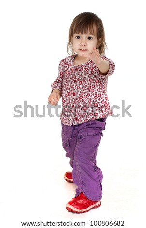 Beautiful good little Caucasian girl posing on a white background