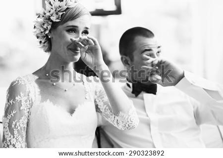 beautiful gorgeous blonde bride and stylish groom crying,  celebrating wedding on the restaurant terrace - stock photo
