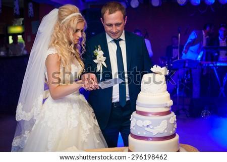 beautiful gorgeous blonde bride and stylish groom cutting colorful cake, celebrating wedding - stock photo