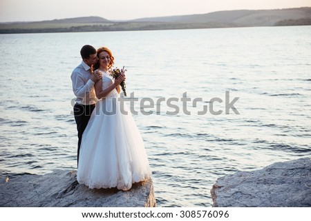 beautiful gorgeous blonde bride and stylish groom on rocks, on the background of a sea - stock photo