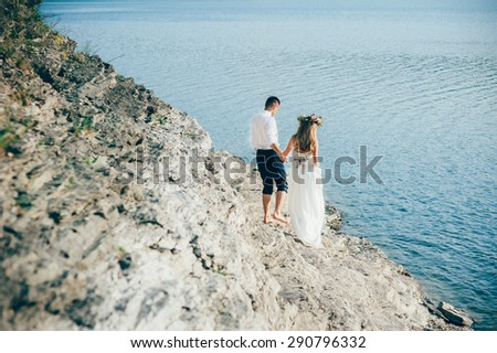 beautiful gorgeous blonde bride and stylish groom, on the background of a sea