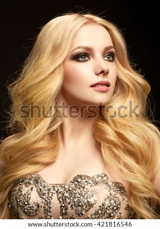 Beautiful gorgeous blonde in a shiny dress. Portrait of a beautiful girl with wavy long hair. - stock photo