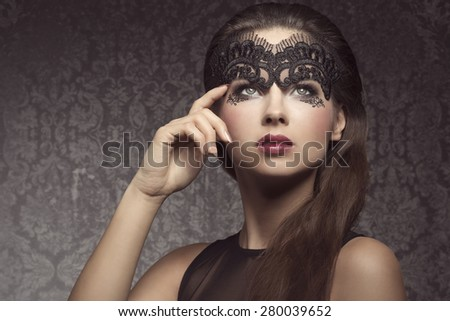 Beautiful, gorgeous, stunning brunette woman with long hair. Wearing transparent, black mask dark make up with little pattern and pink lips.  - stock photo